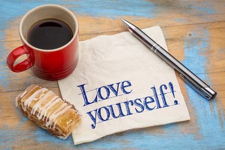 validate: Love yourself advice - handwriting on a napkin with a cup of espresso coffee and cookie against grunge painted wood