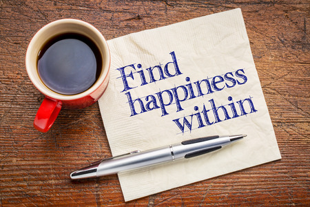 Find happiness within advice - handwriting on a napkin with cup of coffee against rustic wood background 版權商用圖片