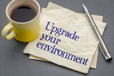 wellness environment: upgrade your environment - handwriting on a napkin with cup of coffee against gray slate stone background