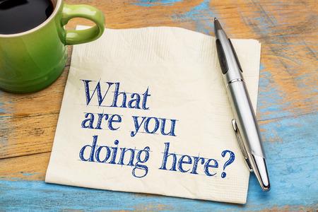-Was machst du hier? Handschrift auf eine Serviette mit einer Tasse Kaffee vor grauem Schiefer Stein Hintergrund