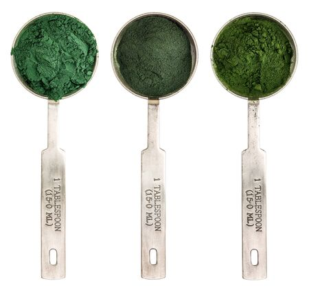 spirulina: Nutrient-rich organic blue green algae, chlorella and spirulina powder - isolated measuring metal tablespoons, top view