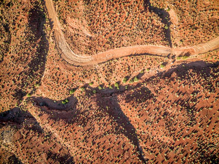 4wd: aerial view of a desert with a 4wd road and coarse vegetation near Moab, Utah - sunrise scenery with long shadows