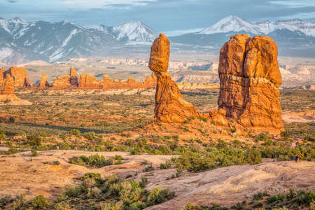 moab: Balanced Rock, WIndows  and La Sal Mountains at sunset with visitors and photographers, Arches National Park, Moab, Utah, USA