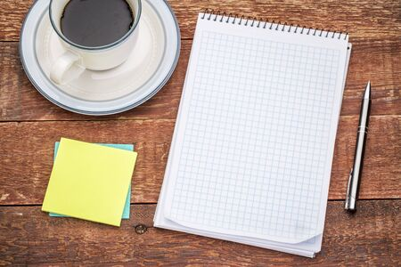 spiral notebook: blank spiral notebook, sticky notes and a cup of coffee against rustic wood Stock Photo