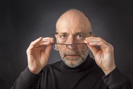 kijken uit over leesbril - headshot van 60 jaar oude man met een baard tegen een zwarte achtergrond