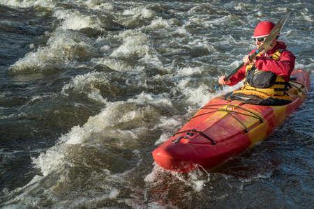 upstream: senior whitewater kayaker paddling upstream the river rapid