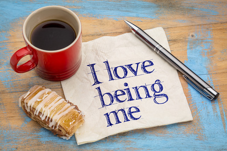 affirmation: I love being me - positive affirmation - handwriting on  napkin with a cup of coffee