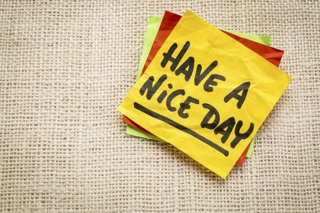 nice day: Have a nice day - handwriting on a sticky note against burlap canvas
