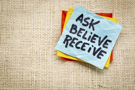 ask, believe, receive - handwriting on a sticky note against burlap canvas Imagens