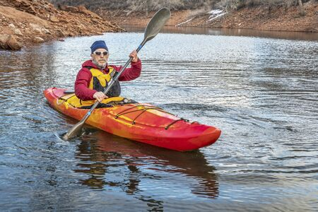 elder tree: senior male is paddling colorful river kayak on a calm lake  - recreation concept Stock Photo