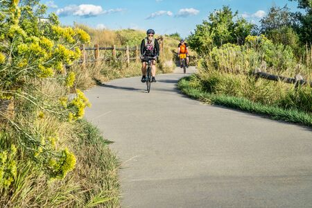 bike trail: WINDSOR, CO, USA, SEPTEMBER 6, 2015: A couple is riding their bikes on the Poudre River Trail - paved path extending more than 20 miles between Timnath and Greeley, late summer morning.