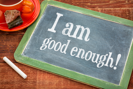 affirmation: I am good enough  - positive affirmation  on a slate blackboard with chalk and cup of tea