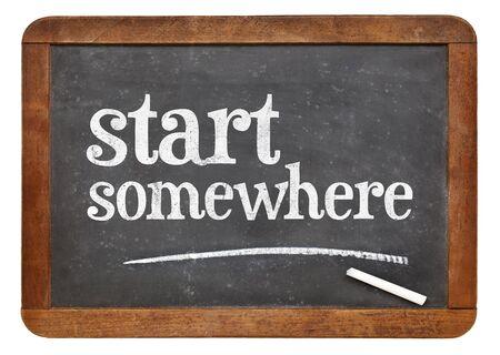 somewhere: Start somewhere  - white chalk text on a vintage slate blackboard