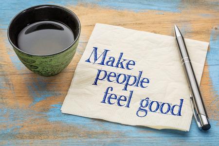 Make people feel good advice - handwriting on a napkin with cup of tea 版權商用圖片