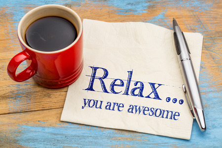 affirmation: Relax, you are awesome - reminder or positive affirmation - handwriting on a napkin with cup of coffee