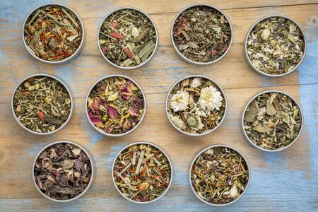 sampler: collection of eleven herbal blend Chinese tea in round metal cans, top view against painted grunge wood with a copy space