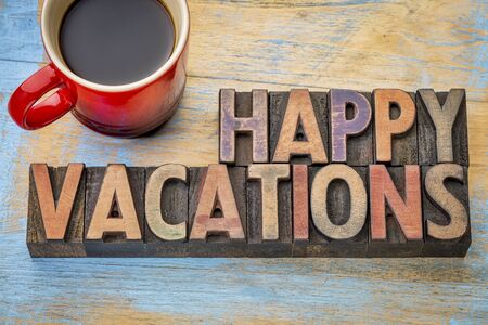 woodtype: Happy vacations  banner in vintage letterpress wood type with a cup of coffee Stock Photo