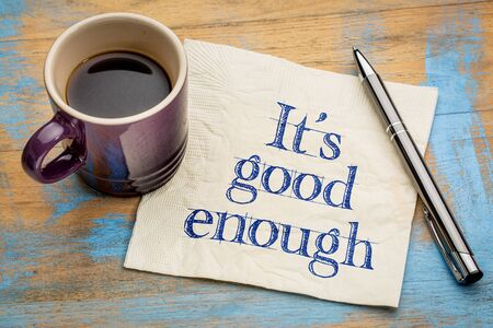 It is good enough - efficiency and productivity concept - handwriting on a napkin with a cup of espresso coffee Imagens