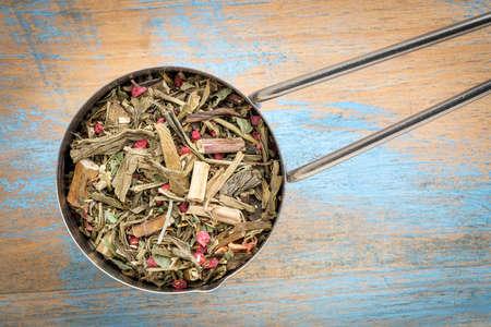 loose leaf: Measuring scoop of a Breathing and bronchitis herbal tea including ginkgo tea, lemon balm, lemon peel and green rooibos