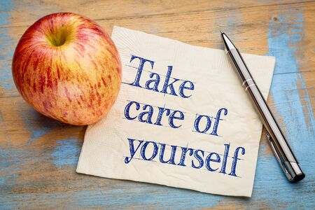 Take care of yourself advice or reminder - handwriting on a napkin with a fresh apple