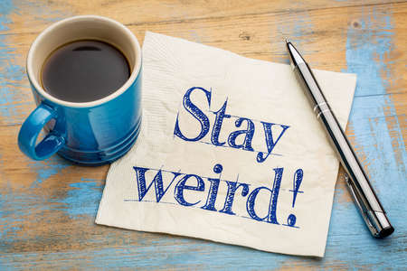Stay weird advice - handwriting on a napkin with a cup of espresso coffee