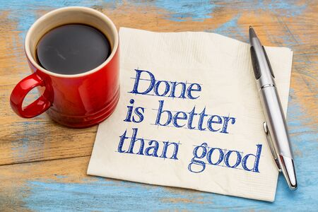 pragmatism: Done is better than good advice ot reminder - handwriting on a napkin with a cup of espresso coffee