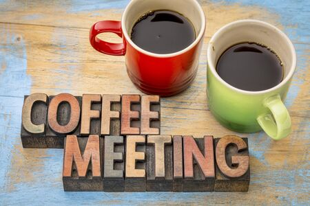 wood type: coffee meeting concept - text in vintage letterpress wood type printing blocks with two cups of coffee Stock Photo
