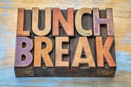bandera hora del almuerzo - el texto en bloques de impresión tipo de madera de tipografía contra la madera pintada grunge Foto de archivo