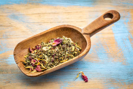 blend: Rustic wooden scoop of healthy stomach herbal tea -  a blend of  peppermint, spearmint, ginger, hibiscus, rosehip, red rose,almond, and osmanthus.