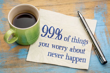 worrying: 99% of things we are worrying about  never happen - handwriting on a napkin with a cup of espresso coffee