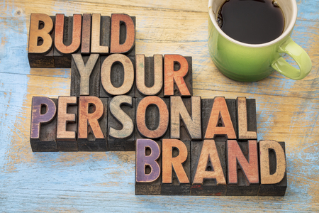 build your personal brand - motivational concept in vintage letterpress wood type block with a cup of coffee Archivio Fotografico