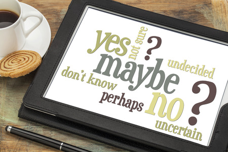 maybe: undecided or uncertain concept - yes, no, maybe  word cloud on a digital tablet with a cup of coffee