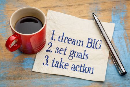 take action: dream big, set goals, take action - inspirational handwriting on a napkin with a cup of coffee