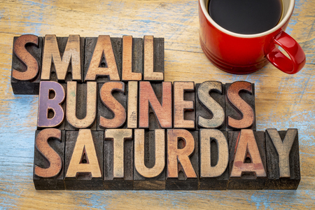 retail business: Small Business Saturday word abstract - text in vintage letterpress wood type with a cup of coffee, holiday shopping concept