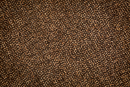 Portuguese corkskin paper background. This versatile, naturally water-resistant paper is hand made in Portugal. Thin layers of dark brown cork are laminated in a tiny grid pattern onto a smooth base sheet.
