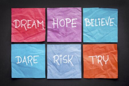 dream, hope, believe, dare, risk, and try - motivational concept - a set of crumpled sticky notes with white handwritten text against black paper background