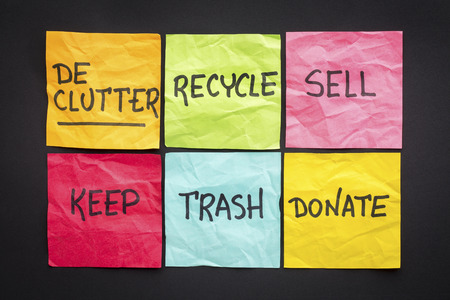 organize: declutter concept (keep, recycle, trash, sell, donate - handwriting on color sticky notes against black paper background