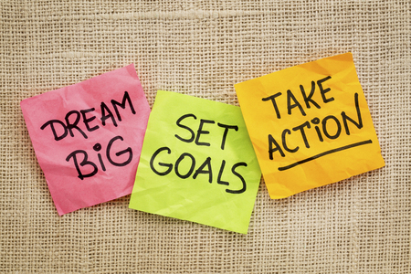 set goals: dream big, set goals, take action - motivational advice or reminder on sticky notes against canvas