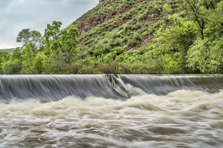 cache la poudre river: diversion dam taking water from river for farmland irrigation; Cache la Poudre River near Fort Collins, Colorado, springtime with high water flow Stock Photo