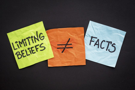 beliefs: limiting beliefs are not facts concept - handwriting on sticky notes against black paper background