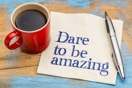 dare: Dare to be amazing - motivational handwriting on a napkin with a cup of coffee