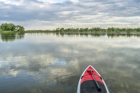 collins: red stand up paddleboard with a paddle on calm lake - Arapaho Bend Natural Area, Fort Collins, Colorado