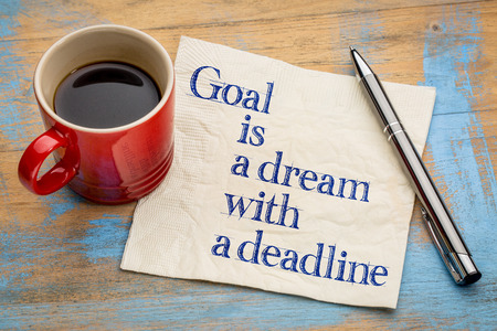 goal setting: goal is a dream with deadline - handwriting on a napkin with a cup of espresso coffee