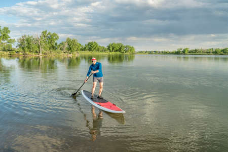 paddler: senior male paddler on a paddleboard, lake in northern Colorado with an early summer scenery
