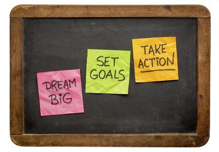 take action: dream big, set goals, take action - motivational advice or reminder on sticky notes against isolated vintage blackboard