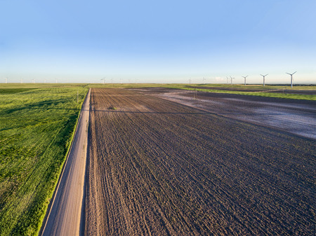 raod: Plowed field, dirt road and windmill farm at Pawnee National Grassland near Grocer, Colorado - early summer aerial view
