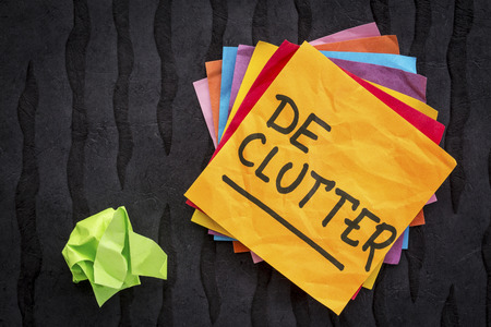 declutter reminder or advice  - handwriting on a sticky note against black Nepalese lokta paper Stok Fotoğraf
