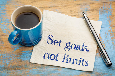 Set goals, no limits reminder or advice. Motivational words on a napkin with a cup of coffee.