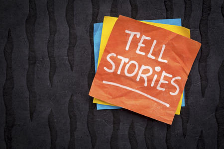 tell stories reminder note - handwriting on a sticky note against black Nepalese lokta paper
