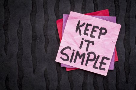 Keep it simple reminder or advice - handwriting on a sticky note against black Nepalese lokta paper Stock Photo